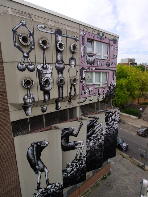 Phlegm paints a large building in Berlin, Germany